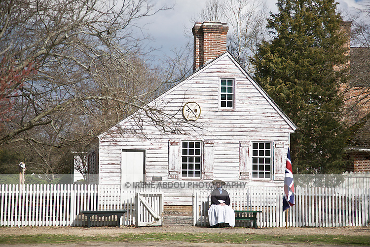 A woman sits outside the gunsmith in Colonial Williamsburg, Virginia.