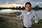 Sebastian Yat, a community leader, stands at sunset in front of the Salinas River in Santa Elena, Guatemala. On the other side of the river is Mexico.