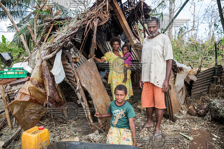 10 year old James with his mother Margaret, his younger sister Ester and his father Amon in front of the remains of their house, which was badly damaged, on 13 March 2015, by Cyclone Pam. Now the family live in a tent provided as part of an international emergency aid effort.