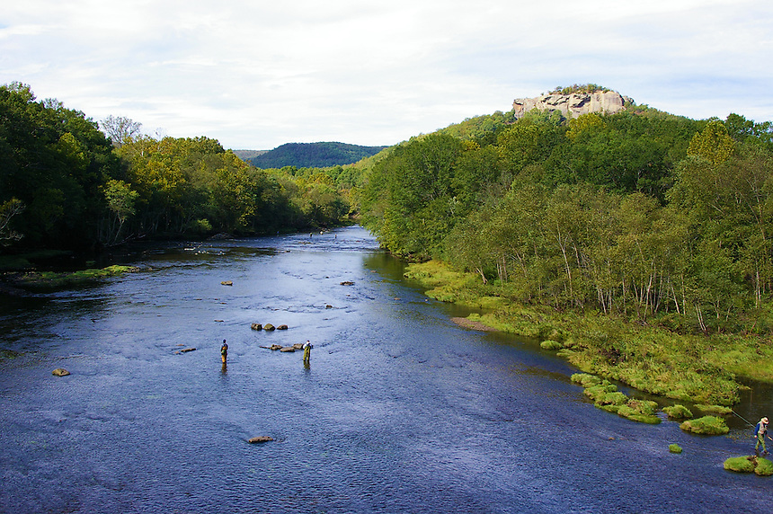 Fly fishermen wading in Little Red River near Heber Springs, Arkansas. Sugarloaf Mountain in background.