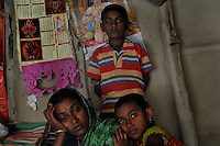 Rita Mandal, 31, with her children sitting inside her house. She is the widow  of late Srinath Mandal (32) who was killed by a tiger on 11th of April 2011. Sunderban, West Bangal, India. April 2011. Arindam Mukherjee
