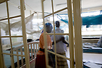 A care giver  escorts a patient into a containement room for people  with TB. Homa Bay, Kenya..