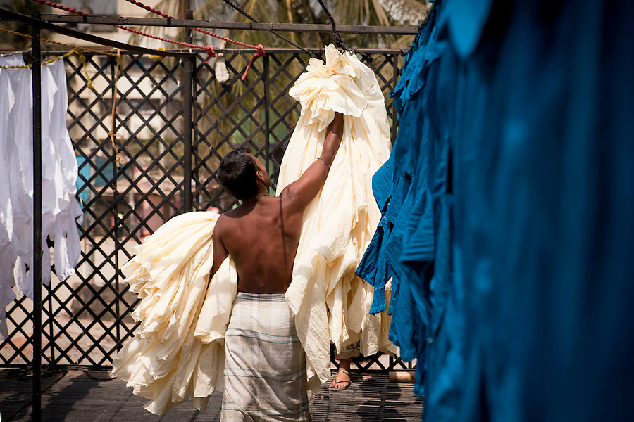 In small clothes dyeing factory in Dhaka, a man collects the sun-dried shirts from the clothing line on the roof. March 3, 2011. Gabriela Barnuevo.
