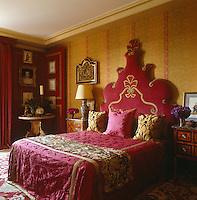 The dramatic headboard in the master bedroom was designed by Alidad in red velvet with damask details