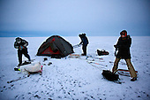 Setting up a tent on the first night of the trek across frozen Lake Baikal in Siberia, Russia. .They are a group of five people: Justin Jin (Chinese-British), Heleen van Geest (Dutch), Nastya and Misha Martynov (Russian) and their Russian guide Arkady. .They pulled their sledges 80 km across the world's deepest lake, taking a break on Olkhon Island. They slept two nights on the ice in -15c. .Baikal, the world's largest lake by volume, contains one-fifth of the earth's fresh water and plunges to a depth of 1,637 metres..The lake is frozen from November to April, allowing people to cross by cars and lorries.