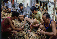 un gruppo di cinesi preparano mazzi di radici