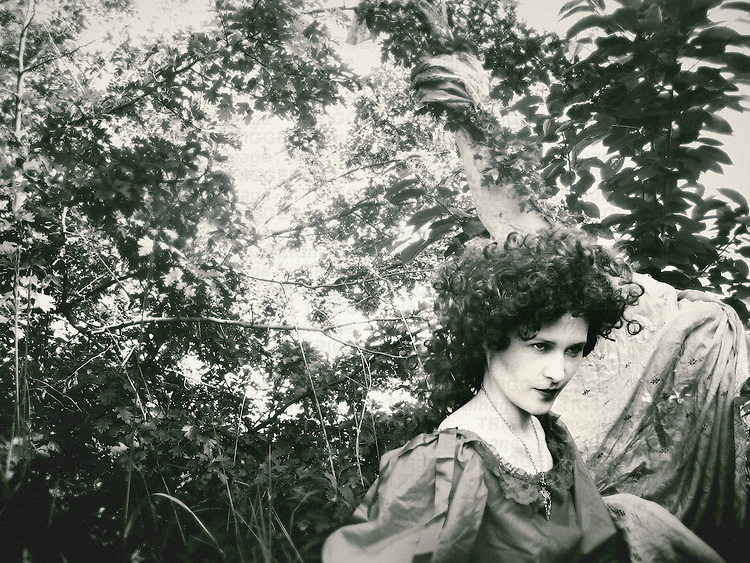 A woman with dark curly hair and angry facial expression, in a vintage gown, seated in front of a floral background.