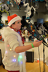 MEREDITH NUSSBAUM reads her original poem from a cell phone during her Spoken Word  performance at the Jingle Boom Holiday Bash, which also had music, windows decorated by artists. Nussbaum wore a Santa hat and fuzzy white sweater with twinkling Christmas lights, and prizes were given to people wearing the most creative or Ugly Sweaters, at the Main Street Gallery of Huntington Arts Council. Sparkboom, an HAC project, provides events such as this geared to Gen-Y, 18-34 years of age, to address the 'brain drain' of creative young professionals of Long Island.
