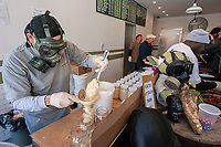 Kris Hofeller wearing a respirator spoons freshly ground horseradish into jars at the Pickle Guys store in the Lower East Side of New York on Sunday, April 2, 2017. Everyone from millennials to former Lower East Sider's descend on the store to buy the freshly ground pungent horseradish to enjoy and to use in Passover seders. The bitter herb brings tears to our eyes and reminds us of the tribulations afflicted on the Jewish people in their flight from Egypt. Passover begins the evening of April 10.  (© Richard B. Levine)