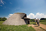 Visitors look at reconstructions of pit dwellings at Sannai-Maruyama, a large settlement  of the early to middle Jomon era, about 5,500 to 4,000 years ago, in Aomori Prefecture, Japan on 12 July 2011..Photographer: Robert Gilhooly