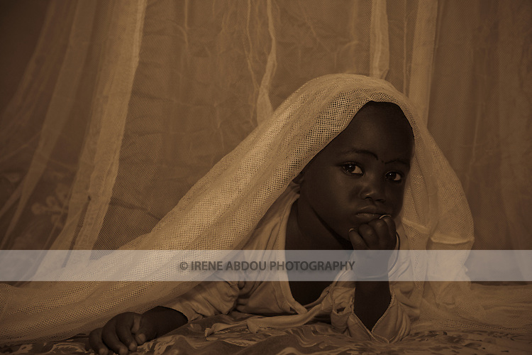 A child in the Garki area of Abuja peeks out from under a Permanet long lasting insecticide treated mosquito net.  Sleeping under a mosquito net every night prevents malaria, which is transmitted through the bite of an infected mosquito.  Globally, malaria kills 1,000,000 people every year, most of them pregnant women and children under five.