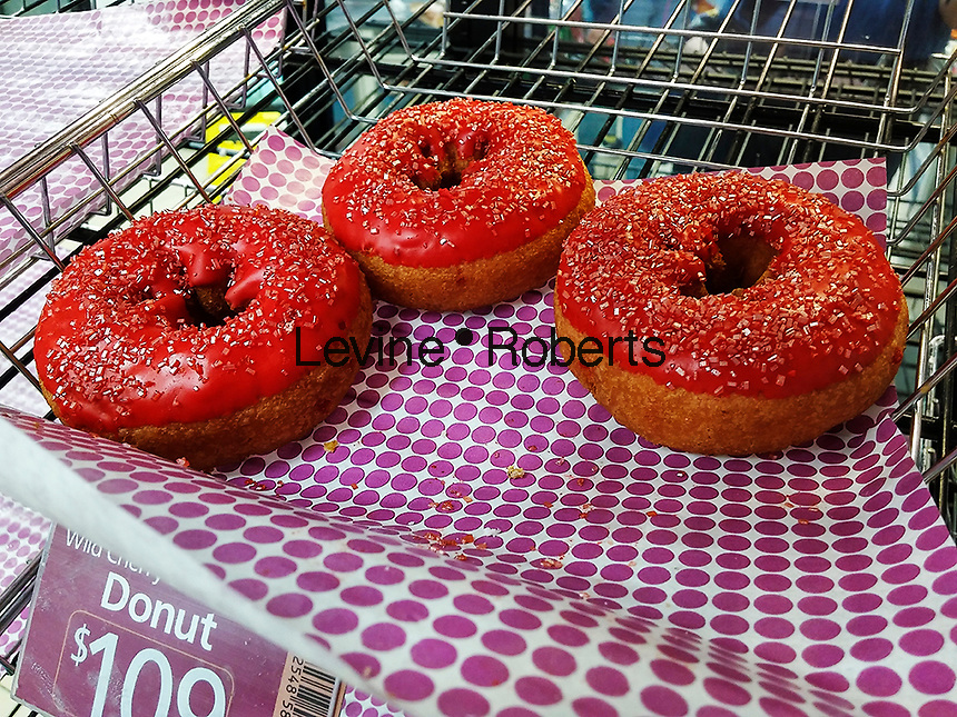 Slurpee doughnuts in a 7-Eleven convenience store in New York on Wednesday, March 23, 2016.  A novelty doughnut from the chain, it is a cake doughnut topped with cherry flavored icing with pink sugar crystals on top of that to emulate the taste sensation of a wild cherry Slurpee, without the brain freeze. The pastry is also colored pink inside with bits of cherry baked in. This year is the 50th anniversary of the Slurpee. (© Richard B. Levine)