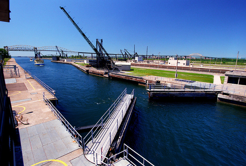 A TOUR BOAT AND A YACHT MOVE OUT OF THE SOO LOCKS ON THE SAINT MARYS RIVER AND INTO LAKE SUPERIOR IN SAULT STE. MARIE MICHIGAN.