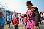 Principal Lal Maya Ale inspects children lined up to begin the day at the Shri Pashupati Praja Primary School in the village of Tanglichowk, in the Gorkha District of Nepal. In the aftermath of the April 2015 earthquake that ravaged Nepal, the ACT Alliance helped people in this village with a variety of services, including latrines, emergency shelter, livelihood projects and school construction.