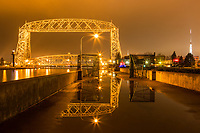 &quot;Aerial Spring Reflections&quot;<br /> The ice has vanished, but rain puddles and fog have reappeared, and the pier gates are open -- sure signs of Spring in Duluth! The iconic Aerial Lift Bridge casts bold reflections in the puddles.