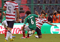 MEXICO CITY, MEXICO - AUGUST 15, 2012:  Herculez Gomez (9) of the USA MNT tackles Manuel Viniegra (6) of  Mexico during an international friendly match at Azteca Stadium, in Mexico City, Mexico on August 15. USA won 1-0.