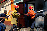 East Timorese firefighters, the Bombeiros, attempt to put out a major fire lit by fueding gangs. Acts of arson across Dili have become a continual occurence. 030606 David Dare Parker