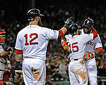Boston Red Sox designated hitter David Ortiz is congratulated by teammates Mike Napoli, left, and Dustin Pedroia after Ortiz hit a solo home run against the St. Louis Cardinals during the seventh inning of Game 1 of the World Series at Fenway Park on Wednesday, October 23, 2013. Photo by Christopher Evans