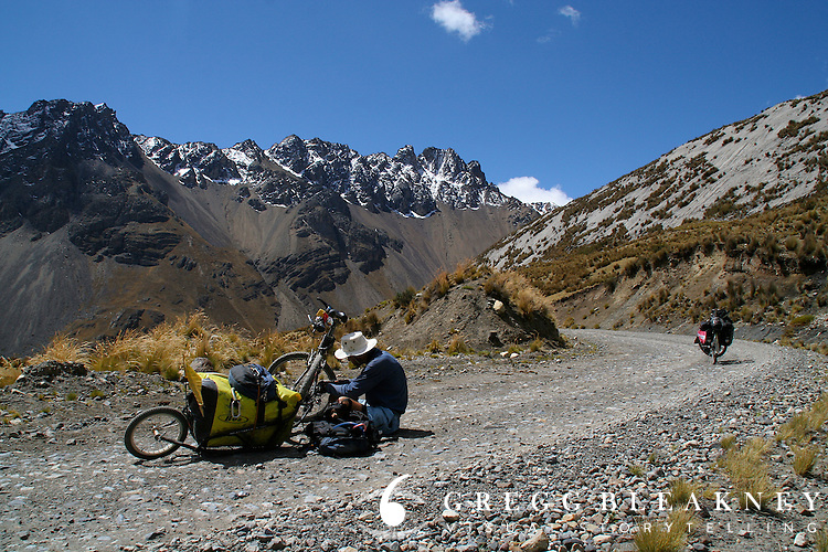 Don Thomas fixes a broken chain without bothering to move his bike off the road--a sign of how light the traffic is in Andean backroads - Huascaran National Park - Cordillera Blanca - Peru - South America