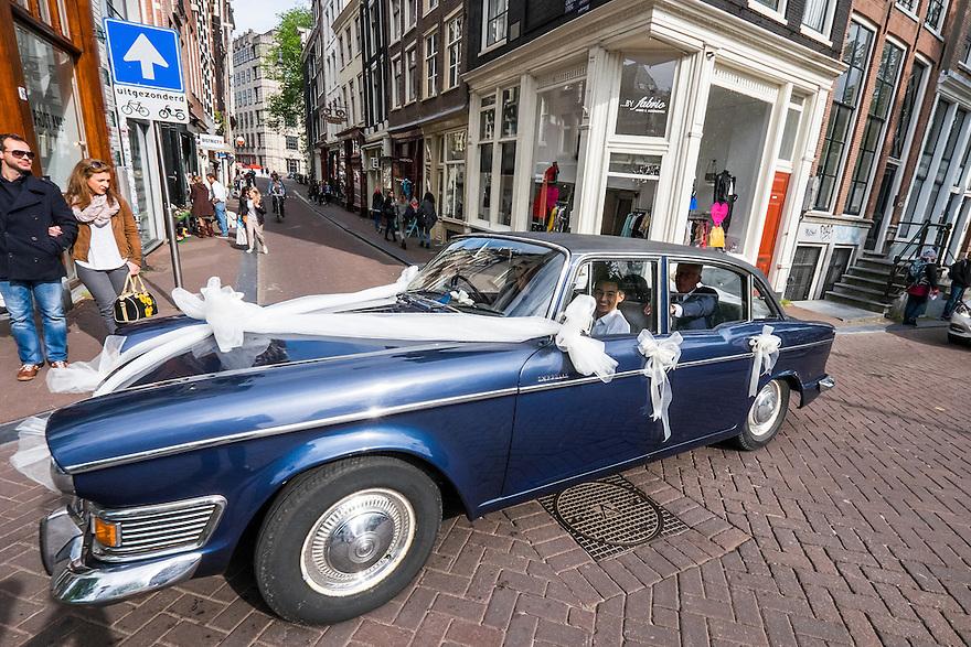 Nederland, Amsterdam, 30 mei 2015<br /> Trouwerij. Auto met pas getrouwd stel rijdt mooi versierd over de gracht.  <br /> Foto: Michiel Wijnbergh