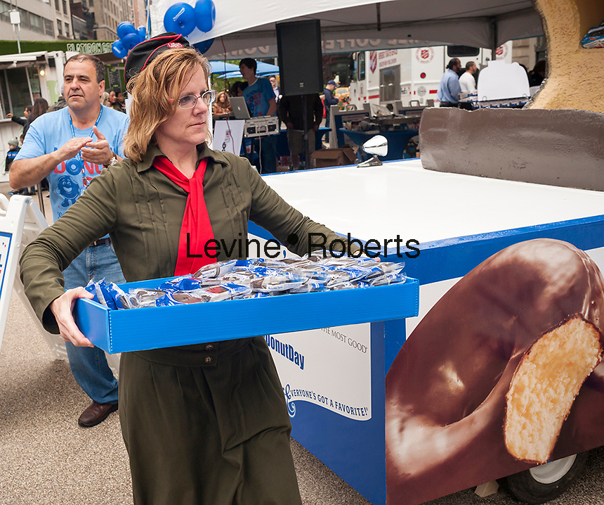 "A ""Donut Lassie"" distributes donuts in Flatiron Plaza in New York for the celebration of National Donut Day on Friday, June 5, 2015. Supported by Entenmann's, the bakers gave out 40,000 chocolate donuts and donated $30,000 to the Salvation Army. National Donut Day, the first Friday in June, was created in 1938 by the Salvation Army to honor the ""donut lassies"" who administered treats and solace to soldiers during WW1. Entenmann's is a division of Bimbo Bakeries USA. (©  Richard B. Levine)"