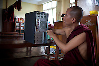 The fairly young head monk at this monastery repairs the computer they use to study for their Buddhist exams. In order to move up, each monk must take a series of exams on the fundementals and tenants of Buddhism.