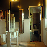 An Arts and Crafts chair in front of a full length mirror in the bathroom is flanked by a pair of protruding glass cabinets