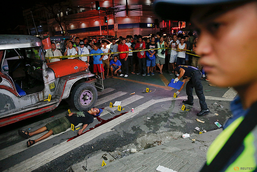 "Onlookers gather as police investigate the scene around a body of a man killed by unknown gunmen in Manila, Philippines early October 18, 2016. A sign on a cardboard found near the body reads, ""Pusher Ako, Wag Tularan"", which translates to ""I am a (drug) pusher, don't be like me.""  REUTERS/Damir Sagolj"