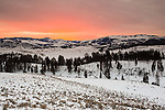 A reddish-orange sunrise colors the clouds in warm tones in Yellowstone National Park, Wyoming.