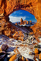 714000094 winter view of turret arch framed through north window arch an iconic scene in arches national park in utah