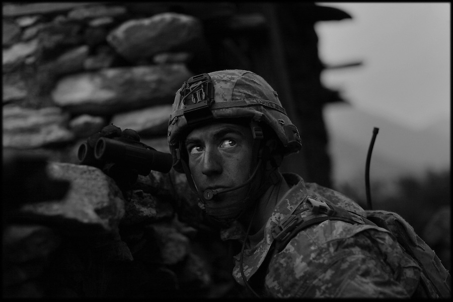 A forward air controller scans the hills for targets as soldiers from Baker Co. 2-12 Infantry Regiment 4th Brigade 4th Infantry Division patrol the slopes and villages of Afghanistan's Korengal Valley in the summer of 2009.