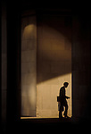 A man walks through the archway in the Federal Triangle in Washington, DC.