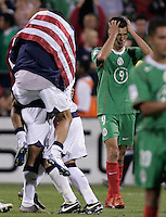 Mexico's Jared Borgetti, right, holds his head, as the USA team celebrates a 2-0 victory over Mexico to clinch a FIFA World Cup berth, in Columbus, OH, Saturday, Sept., 3, 2005.