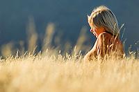 girl sitting in golden grass in Arthur's Pass, New Zealand