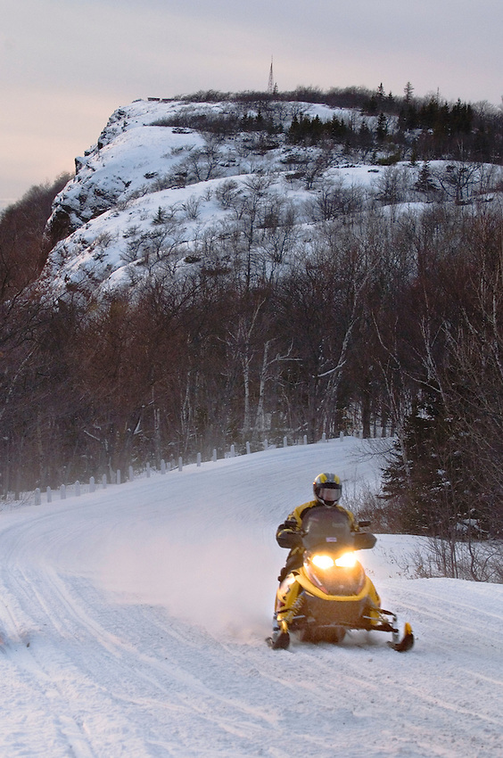 A snowmobiler travels on Brockway Mountain at dusk near Copper Harbor on the Keweenaw Peninsula of Michigan's Upper Peninsula.