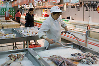Shop assistant at fresh fish counter in supermarket in Chongqing, China