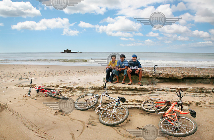 Three boys with their bicycles on Marsella Beach near San Juan del Sur on the Pacific coast.