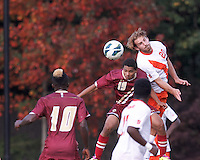 Boston College forward/midfielder Zeiko Lewis (19) and Syracuse University defender Chris Makowski (20) battle for head ball. Boston College (maroon) defeated Syracuse University (white/orange), 3-2, at Newton Campus Field, on October 8, 2013.