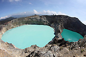 Colorful crater lakes on Kelimutu Volcano, Flores Island, Indonesia. Kelimutu has three lakes: Tiwu Ata Mbupu (Lake of Old People), Tiwu Nua Muri Kofah (Lake of Young Men and Maidens) and Tiwu Ata Polo (Bewitched Lake). The two latter lakes are highly acidic due to underwater fumarole activity and are turquoise in color.