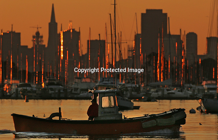 A fisherman slowly motor his way into Sausalito harbor during sunrise.