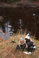 A FLY FISHERMAN TAKES A BREAK WITH HIS DOG WHILE FISHING ON THE EAST BRANCH OF THE ESCANABA RIVER NEAR GWINN MICHIGAN.