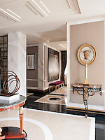 The entrance hallway of a stylish, spacious apartment. Walls covered in marbleised hand painted paper and a polished floor creates an atmosphere where classic and modern elements coexist comfortably in a totally contemporary space.