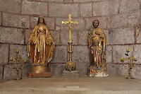Relics, candleabra and crucifix in a chapel in the North transept of the Abbatiale Sainte-Foy de Conques or Abbey-church of Saint-Foy, Conques, Aveyron, Midi-Pyrenees, France, a Romanesque abbey church begun 1050 under abbot Odolric to house the remains of St Foy, a 4th century female martyr. The church is on the pilgrimage route to Santiago da Compostela, and is listed as a historic monument and a UNESCO World Heritage Site. Picture by Manuel Cohen