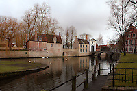 BRUGES, BELGIUM - FEBRUARY 08 : A general view of the 'Beguinage' along the canals of Bruge on February 08, 2009 in Bruges, Western Flanders, Belgium. The 'Beguinage of the Vineyard' was founded in the first half of the 13th century during the reign of Margaret of Constantinople. White swans are floating on the dark waters of the canal reflecting the cloudy sky. (Photo by Manuel Cohen)