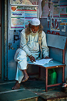 A man sits and reads his book just outside the tomb of Nizamuddin