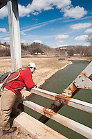 An angler on a bridge overlooking the Green River a trout stream in the Driftless Area of southwestern Wisconsin.