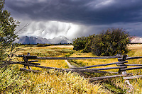 A Jackson Hole thunderstorm add beauty to the already stunning Grand Tetons. The buckrail fence a one of the few remaining relics of Grand Teton Park's western heritage.