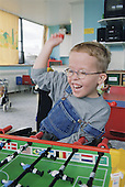 Young boy with Cerebral Palsy sitting in wheelchair playing table football on Children's ward in hospital.  MR