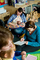 A mother breastfeeding her baby at a drop-in breastfeeding support centre while the breastfeeding consultant takes some notes from another mother.<br /> <br /> Image from the &quot;We Do It In Public&quot; documentary photography project collection: <br />  www.breastfeedinginpublic.co.uk<br /> <br /> Dorset, England, UK<br /> 17/04/2013