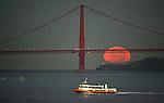 The full moon set behind the Golden Gate Bridge as seen from San Francisco Treasure Island, California.